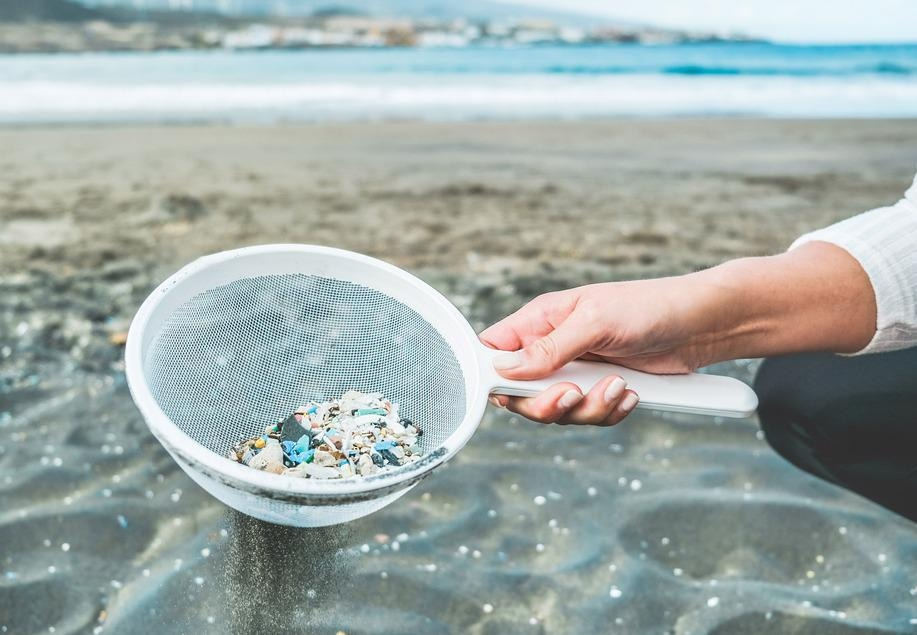 woman cleaning microplastics from ocean sand